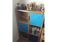 Oak storage unit with different shades of blues doors.