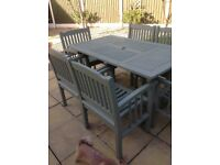 Garden solid wood table and six chairs including large parasol in cream and cushions .