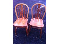 Two sets of two pine dining chairs