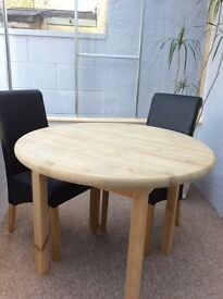 Round rustic farmhouse table plus two faux black leather chairs