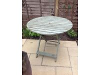 A wooden, slatted , fold down Garden Table