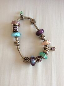 Pandora bracelet and 12 charms, plus 2 safety clips. Hardly worn. Mainly purple and pink.