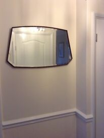 1930's mirror set in a solid sculptured wooden frame