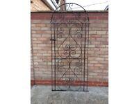 Tall wrought iron garden gate.