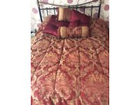 Burgundy double bedspread with pillows, and coordinating curtains