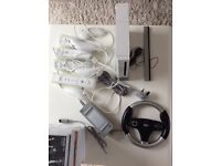 Nintendo Wii + 4 controllers + 4 joysticks + motion bar + 15 games + 2 wheels + 2 gun holders
