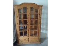 Scandinavian Pine display cabinet with glass doors and drawers underneath.