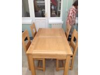 Extendable oak table with 4 oak chairs wilh leather cushion