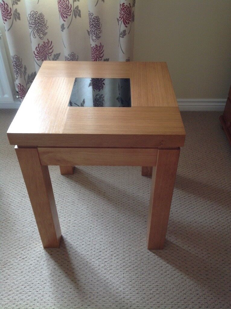 Wooden side table with black glass insert.