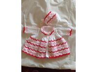 Hand knitted baby cardigan & bonnet, shown made with white, pink & red wool.