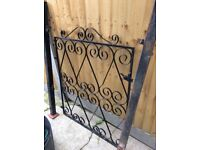 Black wrought iron front gate with 2 metal gate posts