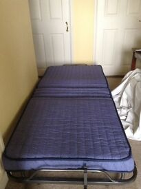 Fold away single bed complete with own protective dust cover
