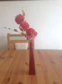 Red glass vase with fake flowers