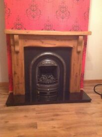 Pine fire surround with cast iron inset and coal effect electric fire