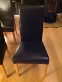 4 Black solid oak and bonded leather dining chairs.