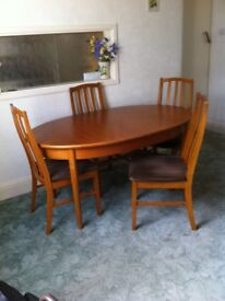 Extending oval dining table in teak with four matching chairs