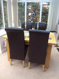 Oak , extending table and six oak and brown leather roll top dining chairs.