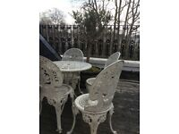 White painted wrought metal garden table (circular) and 4 chairs