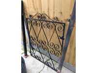 Black wrought iron front gate with metal posts