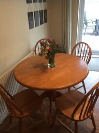 Ercol style dining table in pine. Includes 4 chairs