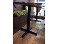 Walnut finished tables with black metal pedestal