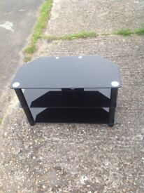 Black glass TV stand for sale in VGC.