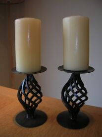 Pair of black metal open twist candle holders with candles