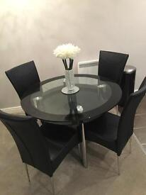 Glass round table and 4 black chairs excellent condition £200 Ono