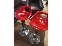 Pair of red bar stools with gas rams.