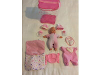Baby doll with eyes that open and close, with accessories and different outfits in own case