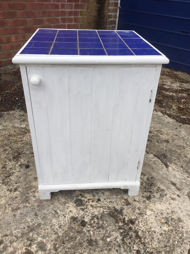 White painted kitchen cupboard with blue tiled top. Delivery available