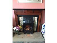 Electric fire with ornate dark wood surround