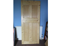 stripped wooden doors and brass handles