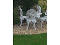 WHITE WROUGHT IRON BISTRO TABLE WITH FOUR CHAIRS.