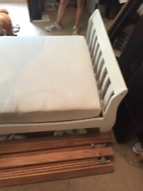 Child's single white wooden bed and mattress