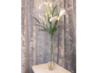 Tall glass vase of faux lilies