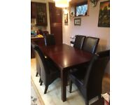 Solid wood dark mahogany extending dining table with six leather chairs