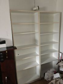 Two white shelving units for books / dvds etc