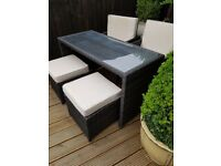 Rattan woven glass top table and 2 chairs and 2 footstools.
