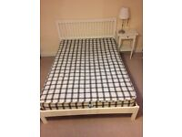 White wooden bed and mattress