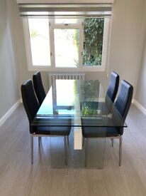 Glass dining room table with dark grey/chrome matching chairs