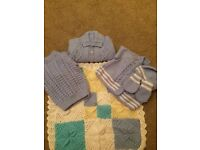 Selection of baby hand knit cardigan s hats blankets and sleeping bags all at a great price