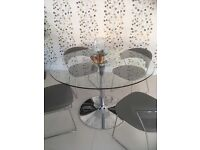 Round, glass dining table from Heals with chrome base.