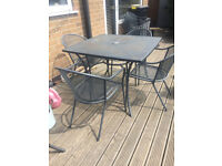 Metal table with four matching chairs - ideal for outdoor use