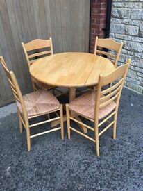 Round drop-leaf rubberwood dining table with 4 wicker chairs