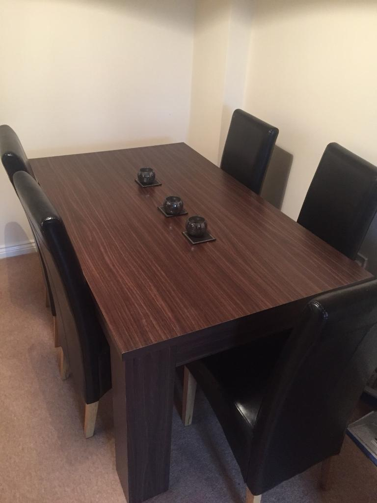 6 seater dining room table in dark wood with 6 dark chairs leather