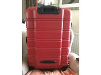 "28"" hard shell red suitcase."