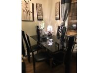 Black glass and silver dining table with 6 chairs.