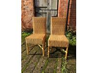 Two wicker dining chairs for sale.