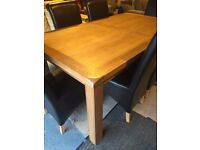 OAK dining table and six leather chairs-never used,only shop showroom